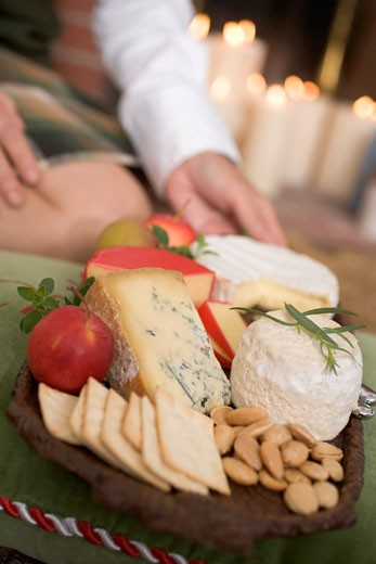Hands serving cheeseboard with fruit and crackers : Stock Photo
