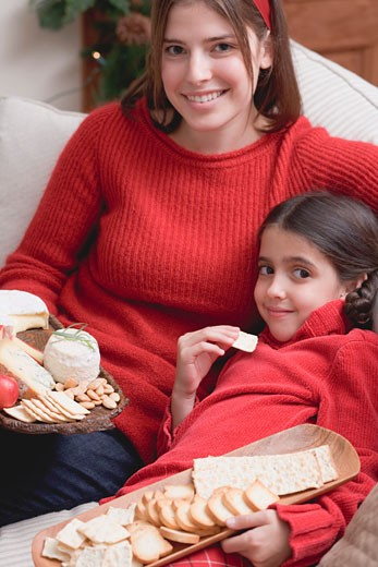 Mother and daughter on sofa with cheeseboard and crackers : Stock Photo