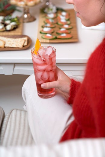 Woman holding glass of Campari with ice cubes, snacks in background : Stock Photo