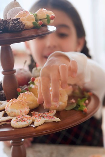 Girl reaching for Christmas biscuit on tiered stand : Stock Photo