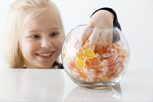 Blond girl reaching into a sweet jar : Stock Photo