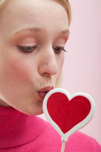 Young woman kissing a heart-shaped lollipop : Stock Photo