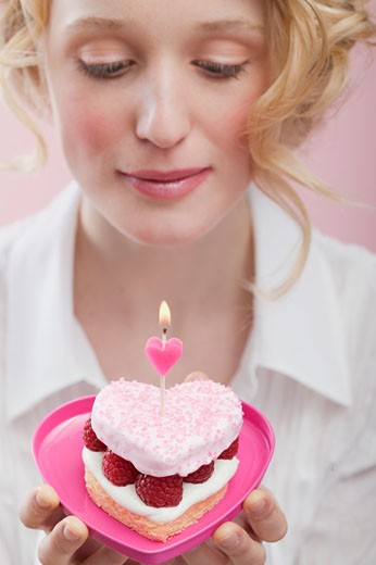 Young woman holding raspberry cake with candle in heart-shaped dish : Stock Photo
