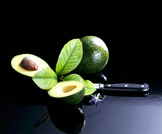 Avocados, whole and halved : Stock Photo