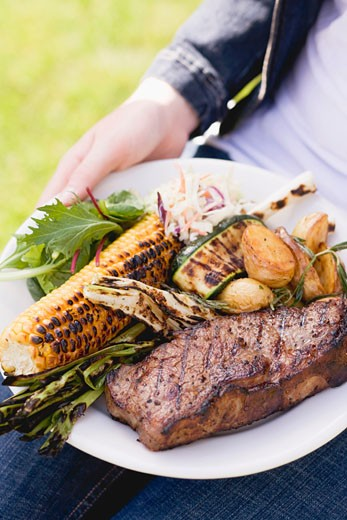 Woman holding plate of steak, grilled vegetables & corn on the cob : Stock Photo
