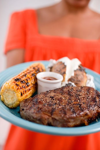 Woman holding plate of steak, corn on the cob, baked potato : Stock Photo