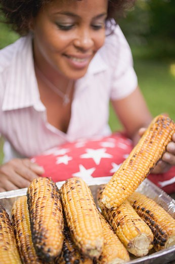 Stock Photo: 1532R-38442 Woman taking grilled corn on the cob out of aluminium dish