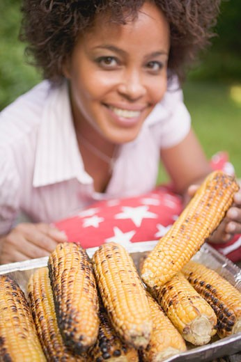Woman taking grilled corn on the cob out of aluminium dish : Stock Photo