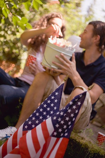 Couple with popcorn in wooden bucket on the 4th of July (USA) : Stock Photo