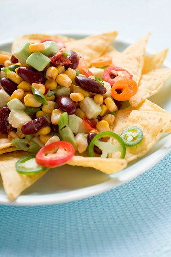 Stock Photo: 1532R-38570 Nachos with beans, sweetcorn, avocado and chilli rings