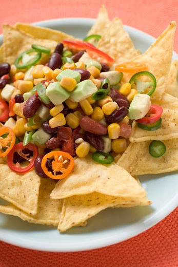 Nachos with beans, sweetcorn, avocado and chilli rings : Stock Photo