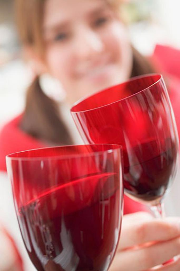 Young woman raising glass of wine (Christmas) : Stock Photo