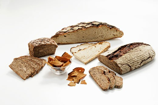 Loaves of wood-oven bread, partly sliced, & toasted bread : Stock Photo