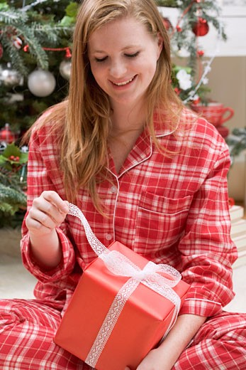 Woman opening Christmas parcel : Stock Photo