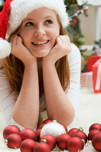 Woman in Father Christmas hat lying on carpet with Xmas baubles : Stock Photo
