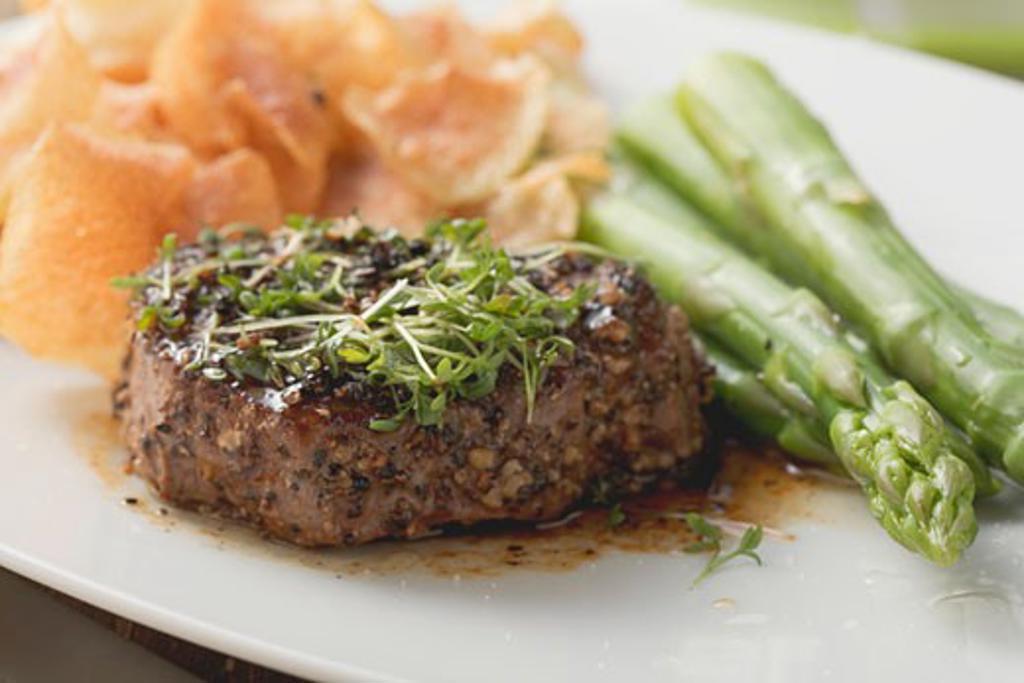 Peppered steak with cress, green asparagus & potato crisps : Stock Photo