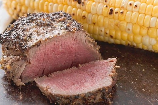 Peppered steak with corn on the cob : Stock Photo