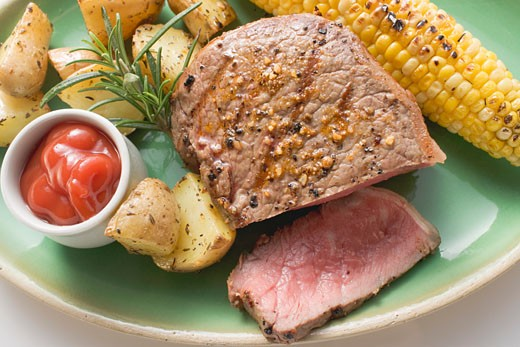 Peppered steak with corn on the cob, roast potatoes & ketchup : Stock Photo