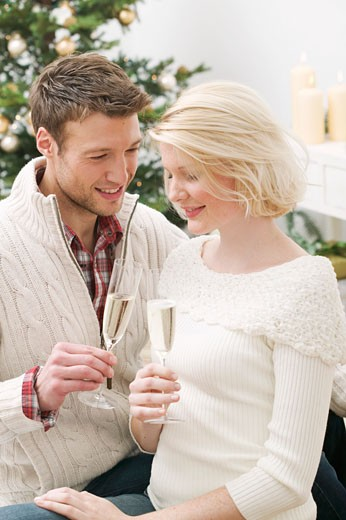 Man & woman clinking glasses of sparkling wine (Christmas) : Stock Photo