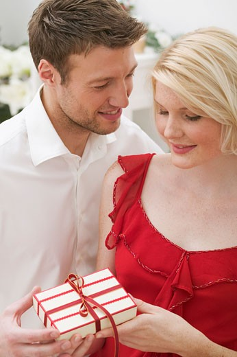 Man giving woman Christmas gift : Stock Photo