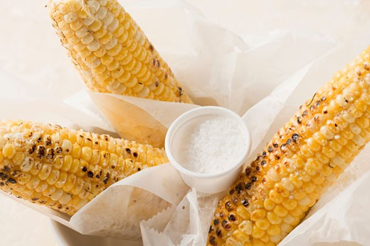 Grilled corn on the cob with salt in greaseproof paper : Stock Photo