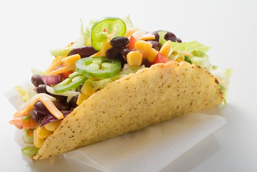 Taco filled with sweetcorn and beans on paper napkin : Stock Photo