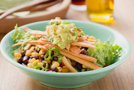 Lettuce, beans, sweetcorn, tortilla strips and guacamole : Stock Photo