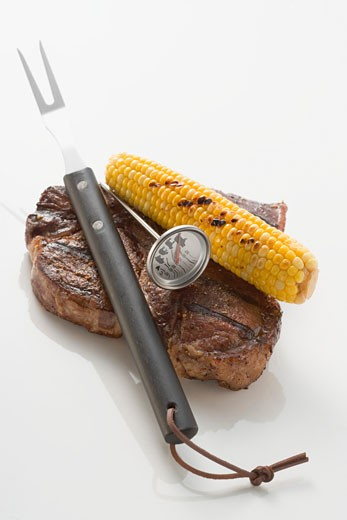 Beef steak with corn on the cob, carving fork & thermometer : Stock Photo