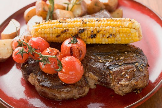 Grilled steak with corn on the cob, cherry tomatoes, potatoes : Stock Photo