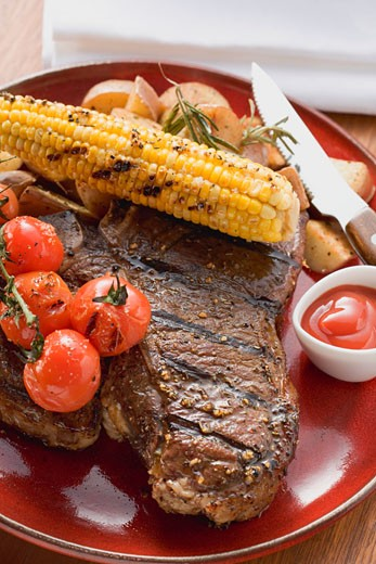 Grilled steak, corn on the cob, cherry tomatoes, potatoes, ketchup : Stock Photo