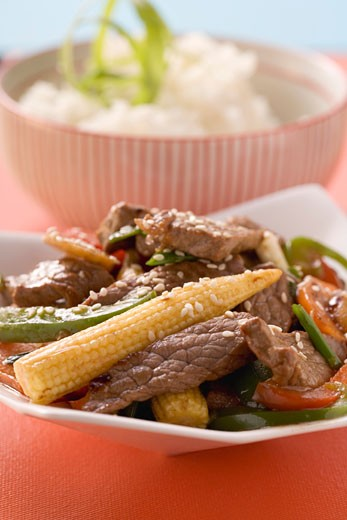 Beef with vegetables & sesame seeds, rice in background (Asia) : Stock Photo