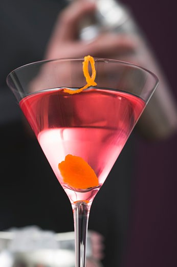 Cosmopolitan in glass, bartender in background : Stock Photo