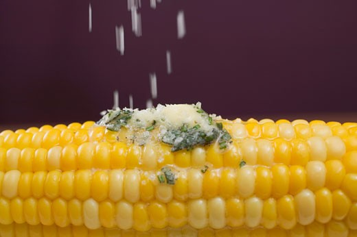 Stock Photo: 1532R-41154 Sprinkling salt on corn on the cob with herb butter