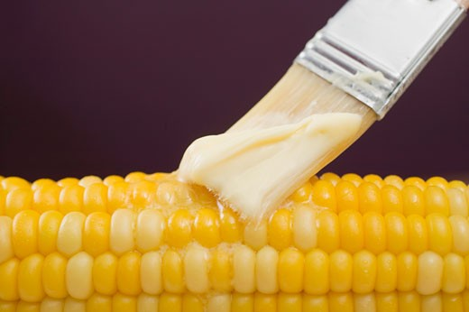 Brushing corn on the cob with butter : Stock Photo
