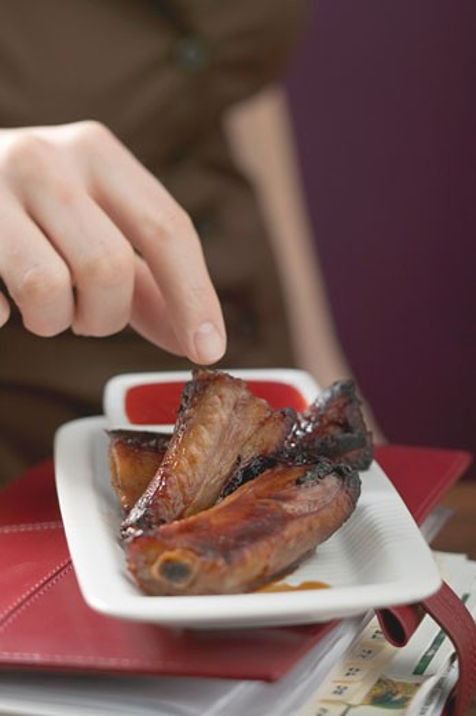 Woman reaching for glazed pork ribs : Stock Photo