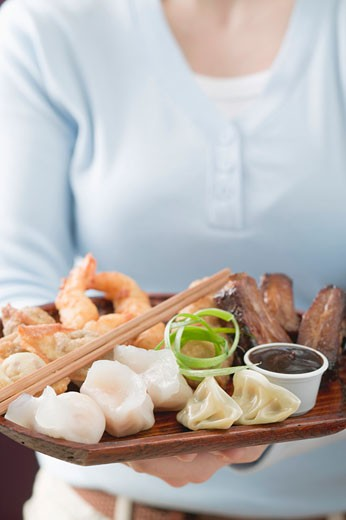 Woman holding Asian appetiser platter : Stock Photo