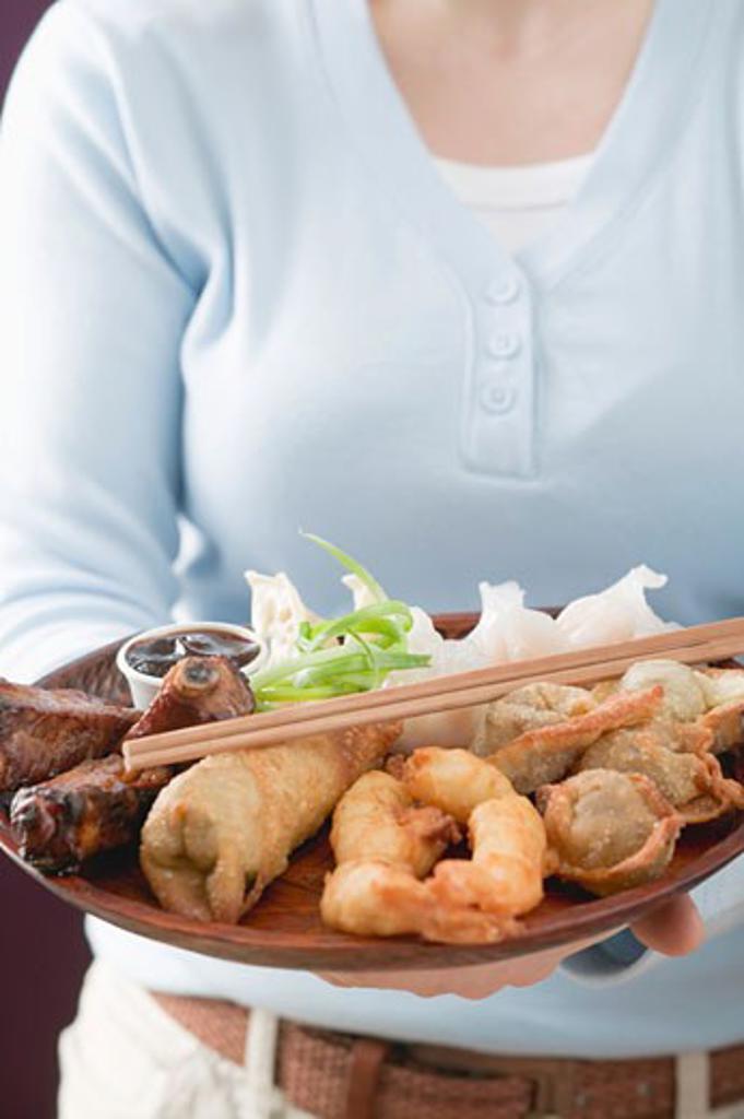 Woman holding Asian appetiser platter : Stock Photo