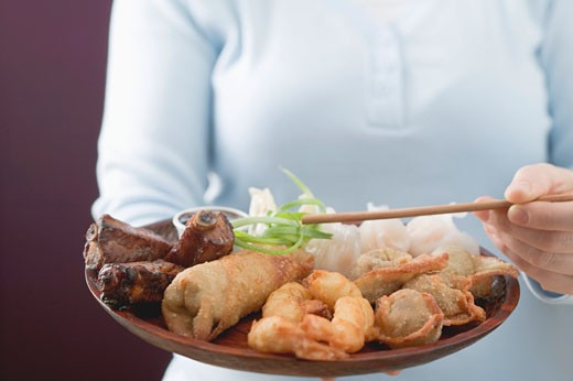 Stock Photo: 1532R-41187 Woman holding Asian appetiser platter and chopsticks