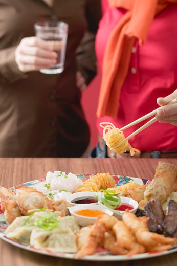 Two women with Asian appetiser platter : Stock Photo