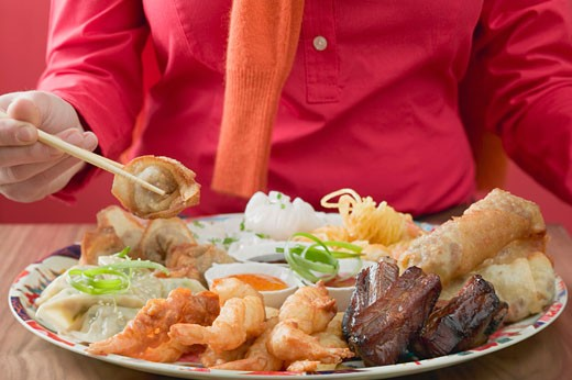 Woman eating Asian appetisers : Stock Photo