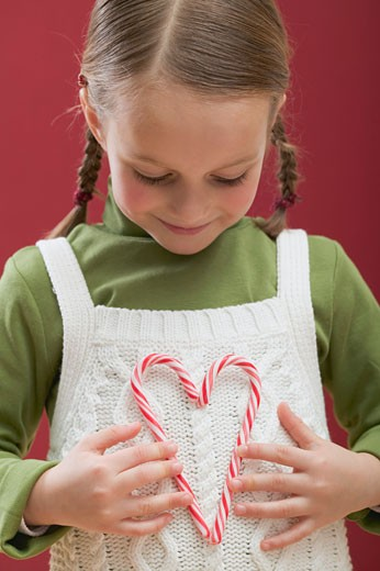 Small girl holding heart made from two candy canes : Stock Photo