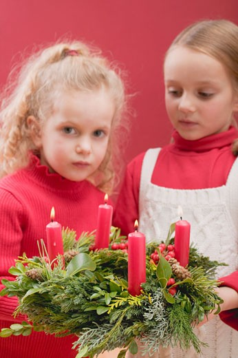 Two small girls holding Advent wreath : Stock Photo
