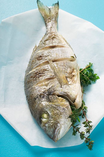 Whole fried sea bream on paper : Stock Photo