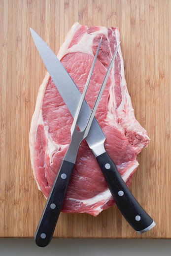 Fresh beef chop with knife and meat fork : Stock Photo