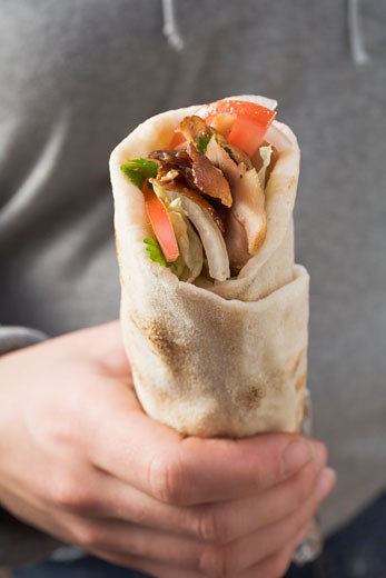 Hand holding a döner wrap : Stock Photo