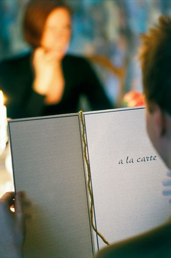 Man reading menu in restaurant with woman in background : Stock Photo