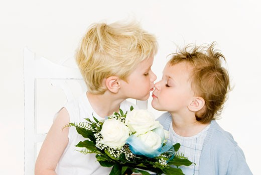 Two children kissing over a bouquet of white roses : Stock Photo