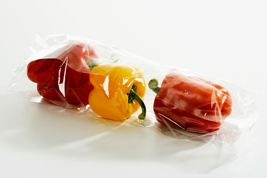 Three peppers in plastic packaging : Stock Photo