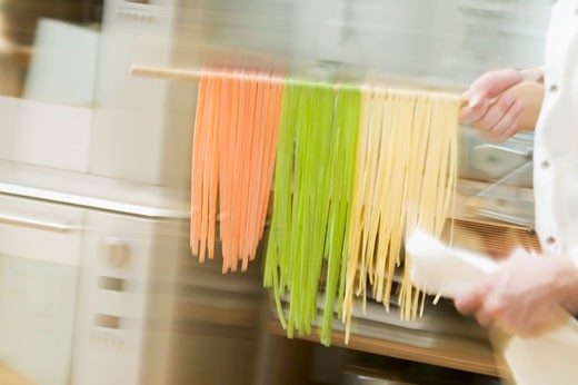 Chef hurrying through kitchen with ribbon pasta on wooden spoon : Stock Photo