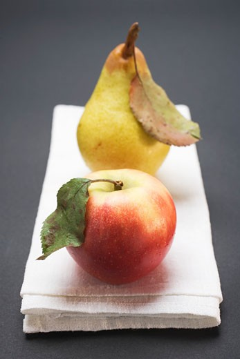 Red apple and pear with leaves on cloth : Stock Photo